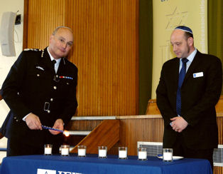 Commissioner lighting a candle with Mathew Shaer, chair of the Jewish Police Association